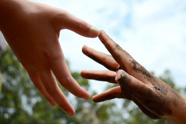giving benefits the giver Middle Class Dad 1 small dirt covered hand reaching up and another hand is reaching down to help