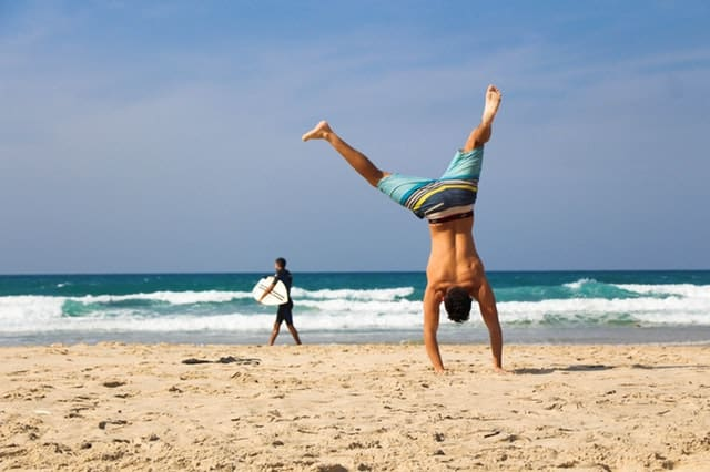 how to reduce cholesterol levels naturally middle class dad guy doing a cartwheel on the beach
