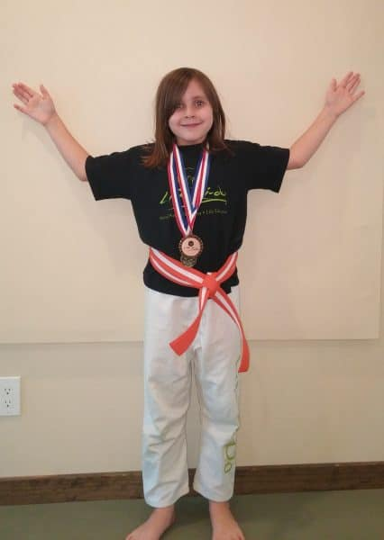 confidence building activities for kids Middle Class Dad Jolie Campbell with medals from a karate tournament