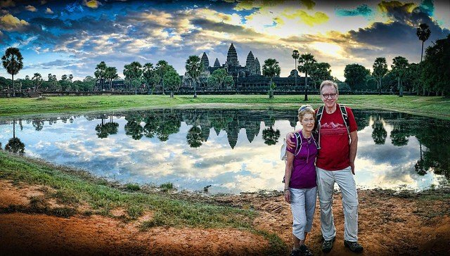 save for retirement older couple standing in Angkor Wat, Cambodia Middle Class Dad