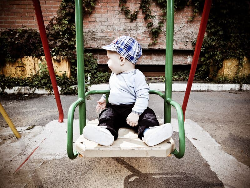common parenting issues Middle Class Dad baby in a cute hat sitting on a swing