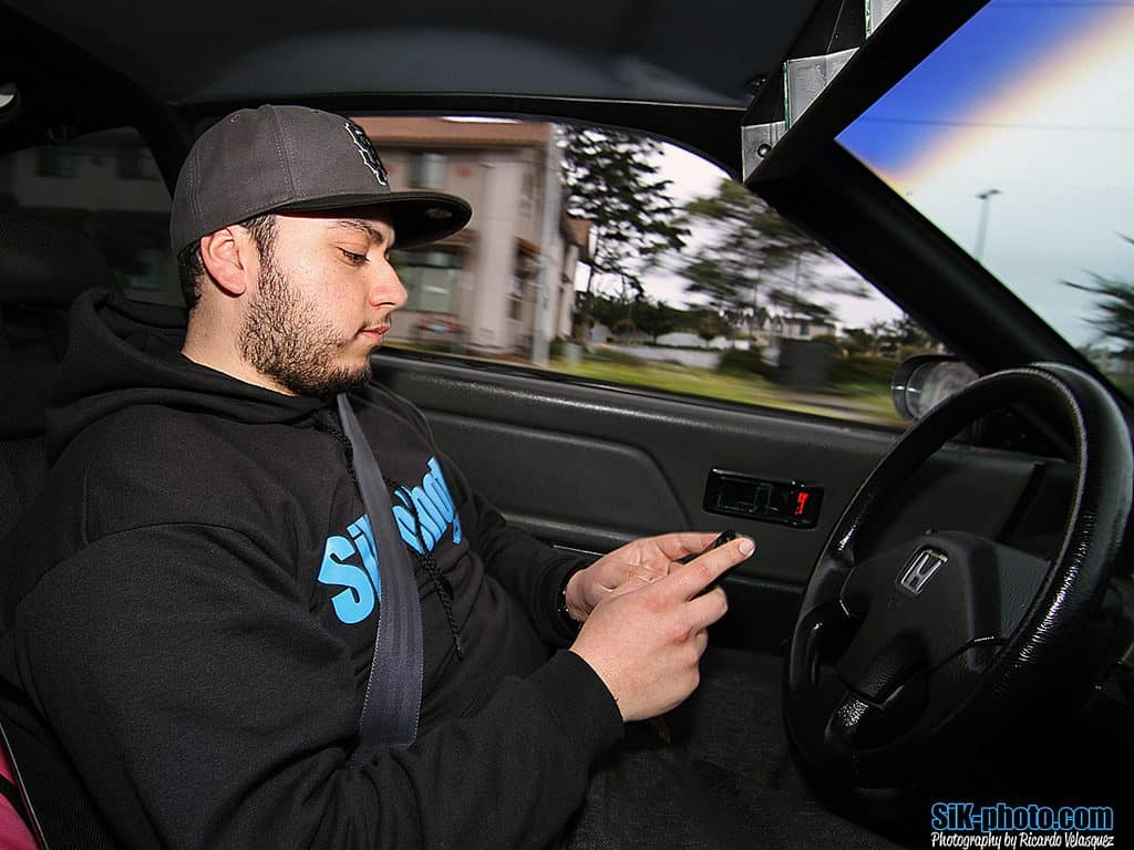 guy texting and driving wearing a hoodie and baseball cap cell phone addiction symptoms Middle Class Dad