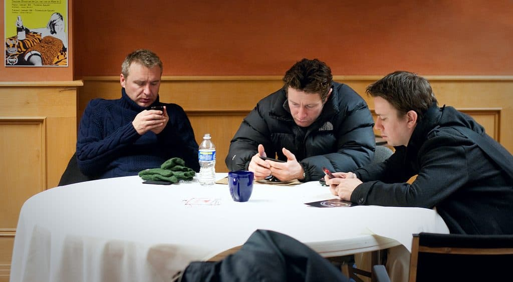3 guys at a dinner table all on smartphones cell phone addiction symptoms Middle Class Dad