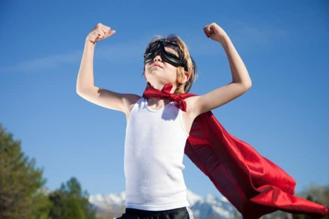 young boy wearing a red cape and mask over his eyes with arms raised up like a superhero overcoming fear of failure Middle Class Dad