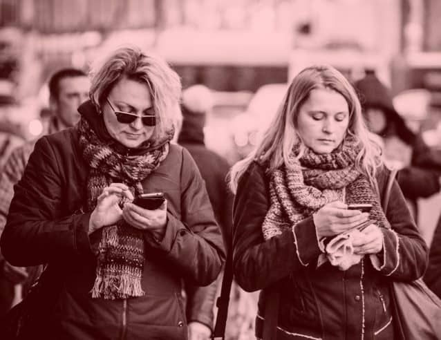 2 ladies on cell phones wearing winter clothes cell phone addiction symptoms Middle Class Dad