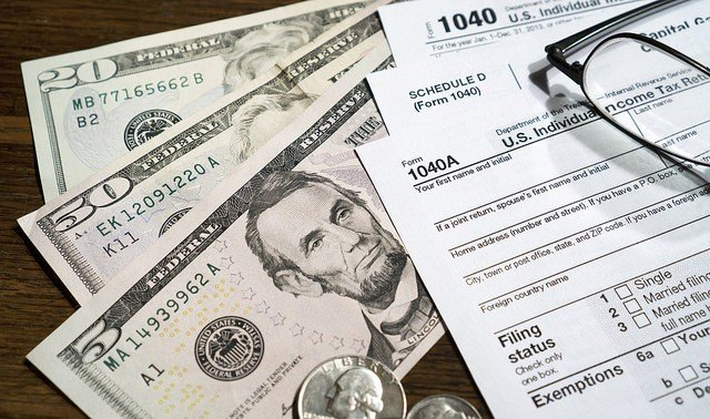 common tax mistakes IRS forms on top of some 5 dollar bills Middle Class Dad