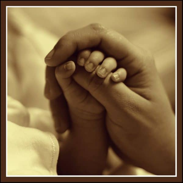 life insurance tips and advice Middle Class Dad sepia colored picture of a young hand being held by an older hand