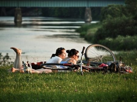 7 stages of a healthy relationship Middle Class Dad 2 women on the banks of a river laying in the grass with bicyles nearby