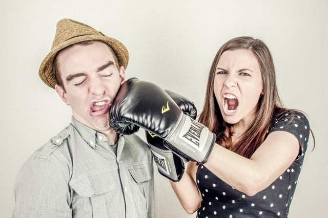Gottman's Four Horsemen Middle Class Dad woman with boxing gloves on punching a guy in a hat