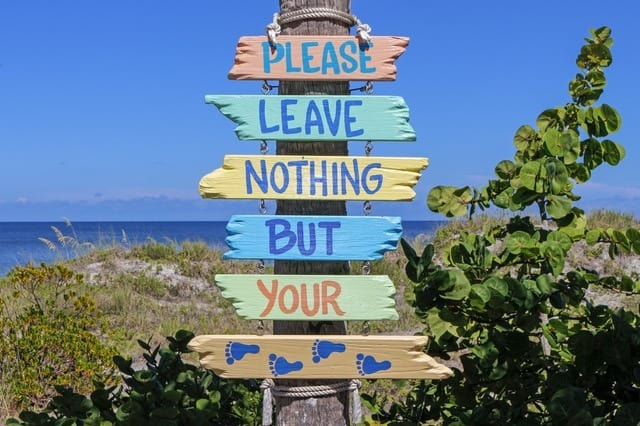 sign near a beach saying please leave nothing but your footprints summer vacation on a budget Middle Class Dad