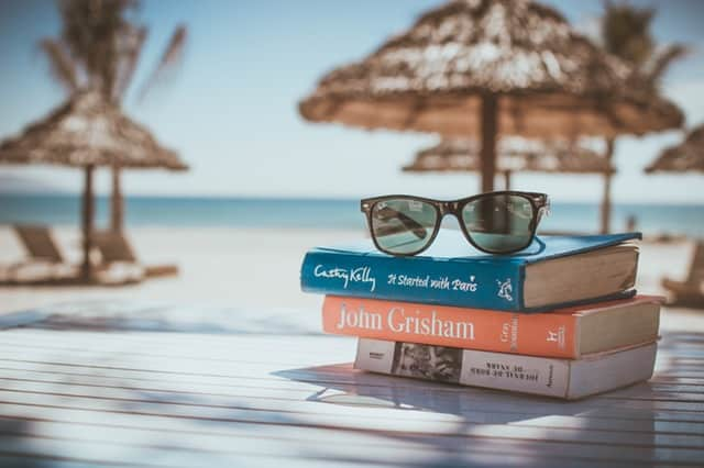 pile of books and a pair of glasses on a table near the beach summer vacation on a budget Middle Class Dad
