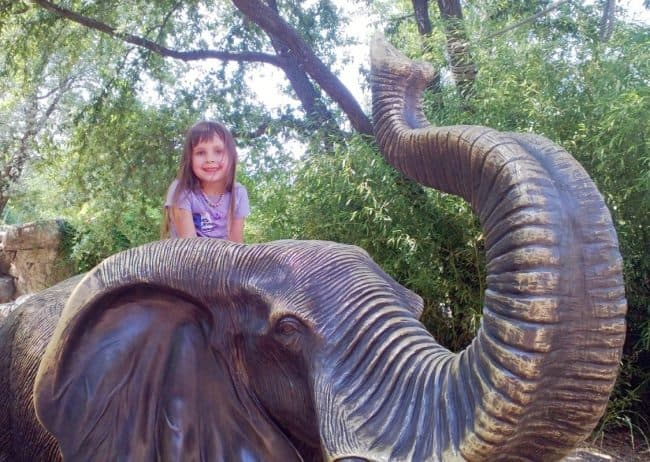 Jolie Campbell on the back of an elephant statue at the Dallas Zoo summer vacation on a budget Middle Class Dad