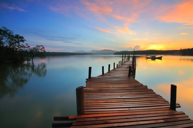 boardwalk dock leading out over a beautiful lake at sunset summer vacation on a budget Middle Class Dad