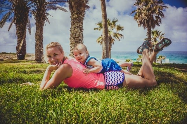 blond mom laying in the grass near the ocean with a baby on her back and palm trees in the background summer vacation on a budget Middle Class Dad