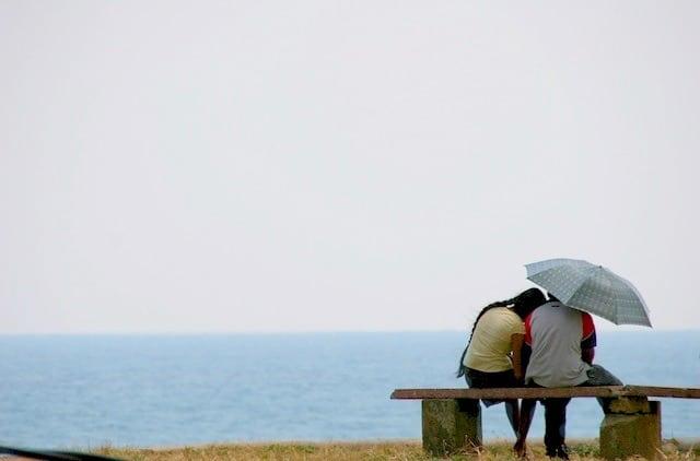 Gottman's Four Horsemen Middle Class Dad couple sitting on a bench under an umbrella by the ocean
