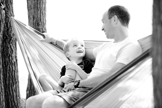 qualities of a good father dad in hammock with kid middle class dad