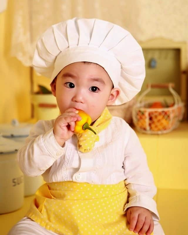 little Asian boy in chef's hat and apron eating a yellow bell pepper healthy eating habits for children Middle Class Dad bio