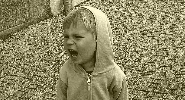 Middle Class Dad child behavior problems and solutions sepia picture of a young boy in a hoodie on a brick street yelling in anger