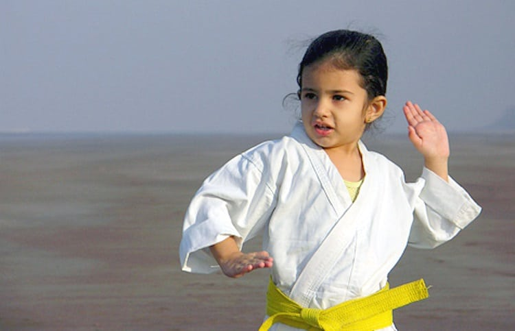 Middle Class Dad how to choose a martial arts school young girl in a karate gi with a yellow belt posing