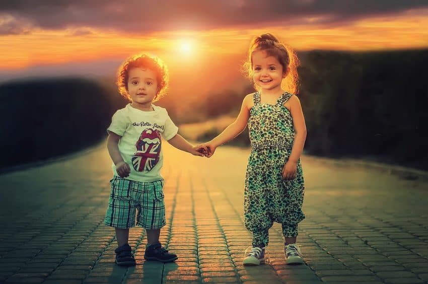 confidence building activities for kids 2 young kids holding hands, smiling, at sunset