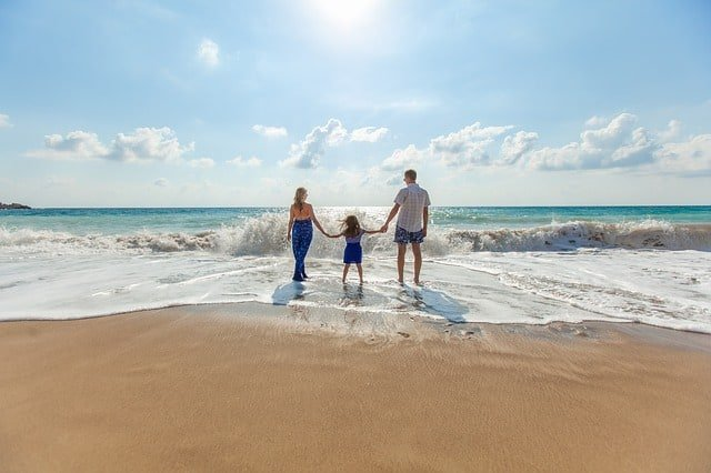 summer family vacation ideas mom, dad and child on a beach Middle Class Dad
