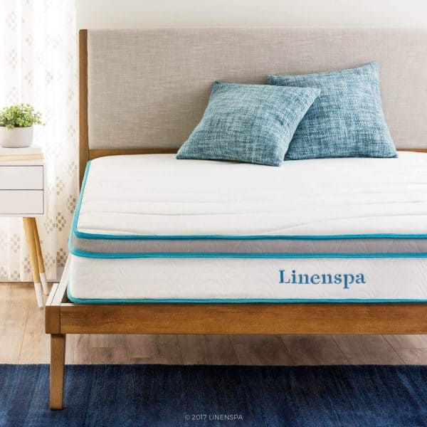 effects of sleep deprivation on students Linenspa mattress on bed with 2 blue throw pillows