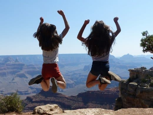 best vacation spots for tweens girls jumping at the Grand Canyon Middle Class Dad