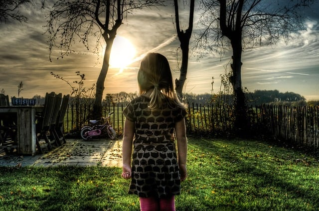 growing up with an alcoholic father Middle Class Dad bleak photo of a lonely girl in the backyard at sunset