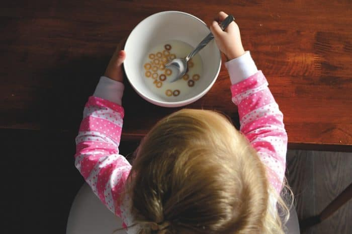 how to overcome picky eating overhead shot of a young child eating Fruit Loops in a bowl Middle Class Dad