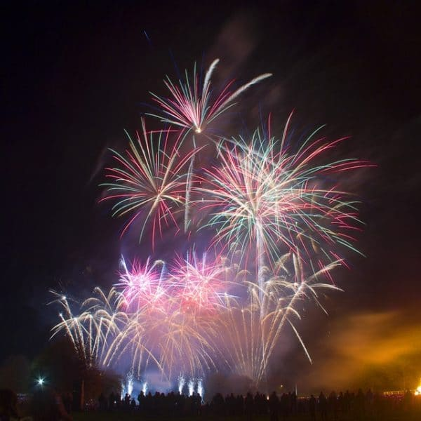 keeping New Year's resolutions rainbow colored fireworks over a big city Middle Class Dad