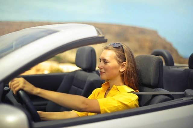 least expensive cars to insure for teenage drivers young woman in a yellow shirt driving a convertible Middle Class Dad
