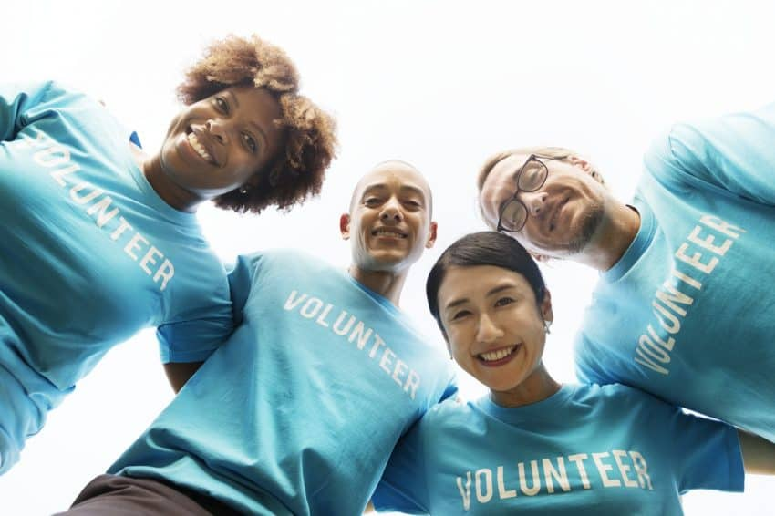 giving benefits the giver Middle Class Dad 4 people wearing light blue Volunteer shirts huddled together