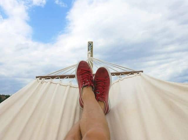 Middle Class Dad earn extra money on the side legs with red sneakers lounging on a hammock with blue sky and clouds in the background