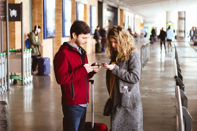 best budget apps for couples Middle Class Dad man and woman both looking at phones in the middle of an airport