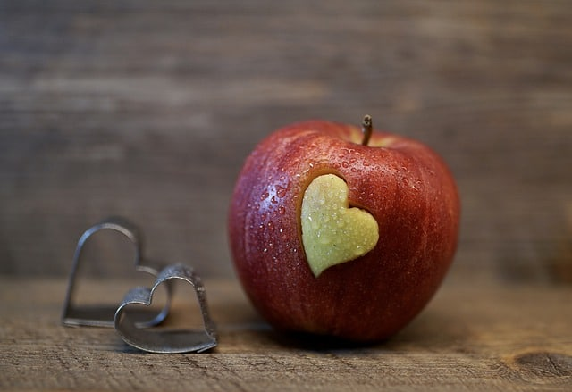 emotionally distant husband signs an apple on a table with 2 heart shaped cookie cutters next to it with a heart shaped bite out of the apple Middle Class Dad