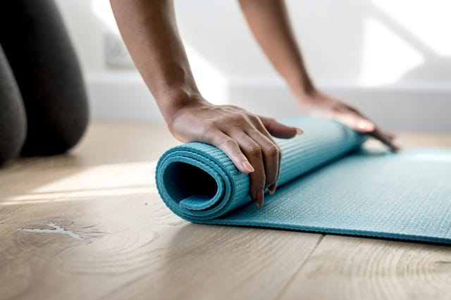 how to get certified in yoga Middle Class Dad woman on the wood floor rolling up a light blue yoga mat