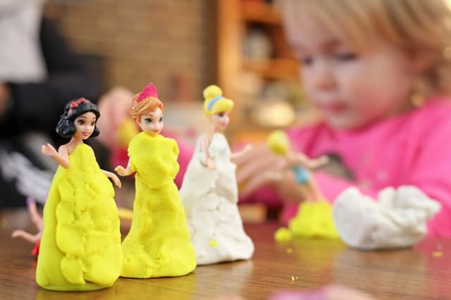 how to encourage your child to play independently young blonde haired girl playing with Disney princess dolls Middle Class Dad