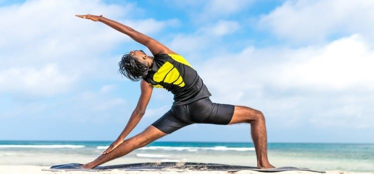 Middle Class Dad yogic breathing benefits man practicing yoga in a black and yellow outfit on the beach