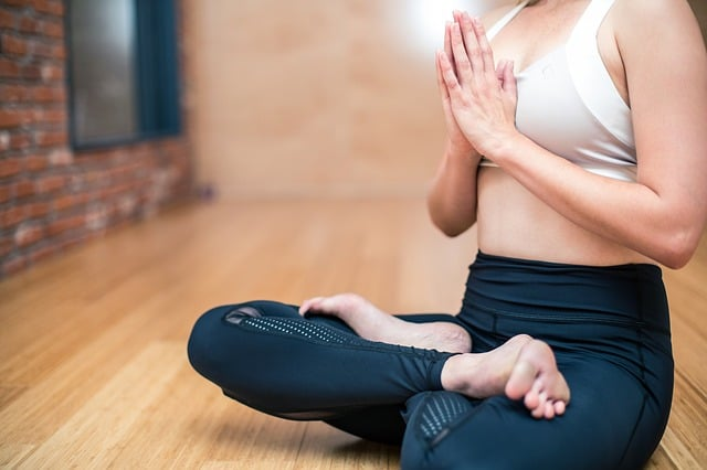 Middle Class Dad yogic breathing benefits woman in seated prayer pose on a hardwood floor