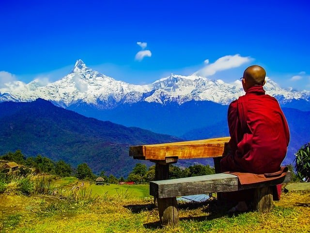 why go on a spiritual retreat Middle Class Dad a monk in a red robe sitting facing a mountain range