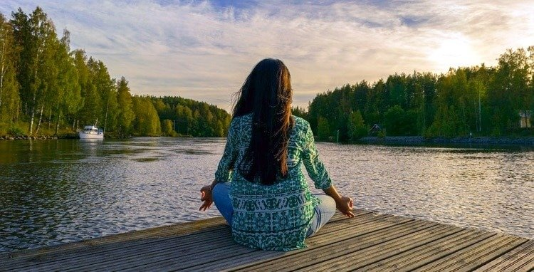 why go on a spiritual retreat Middle Class Dad woman meditating on a dock at the edge of a lake