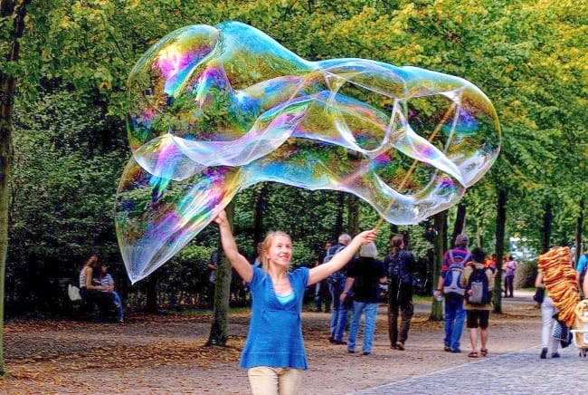low-cost summer family fun ideas a woman with a bubble wand making giant bubbles in a park Middle Class Dad