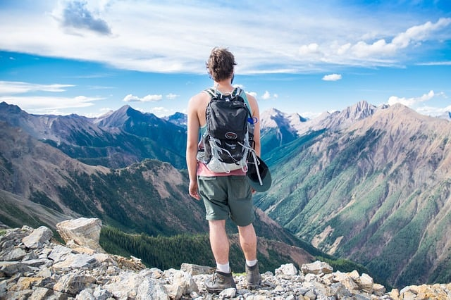 what is trekking all about? Middle Class Dad man in shorts on top of a mountain overlooking more mountains